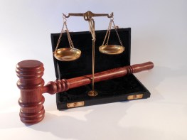 an image of a gavel and the scales of justice which represents weighing one thing against its opposite such as legal vs. criminal