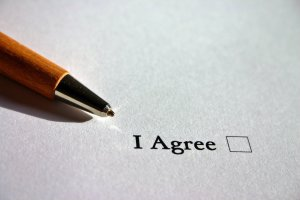 image of a hand holding a pen ready to check a box that says I Agree to signify a commitment