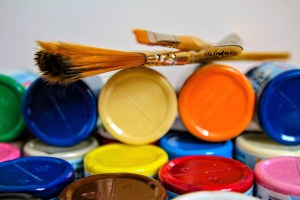 two paint brushes and various color paints to indicate how brushing a view point over a situation will color the way it looks