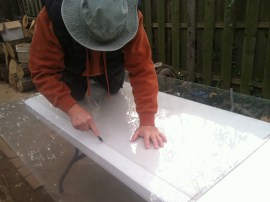 Cutting plexiglass sheets to the right dimension for our frame.