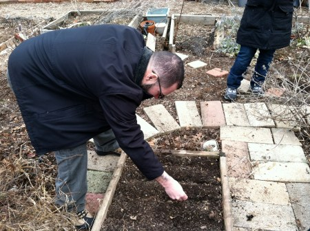 Enrique planting lettuce in our raised bed.