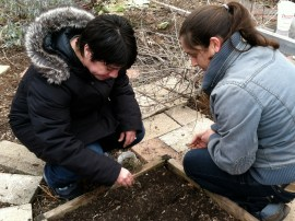 Raíces co-director planting donated seeds in the with garden volunteer Marisol Gonzalez in the Raíces EcoCulture garden plots.