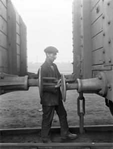 Worker between two wagons, coupling them.