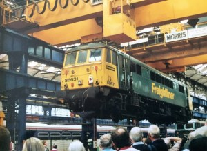 Electric locomotive being listed by pair cranes at Crewe Woeks