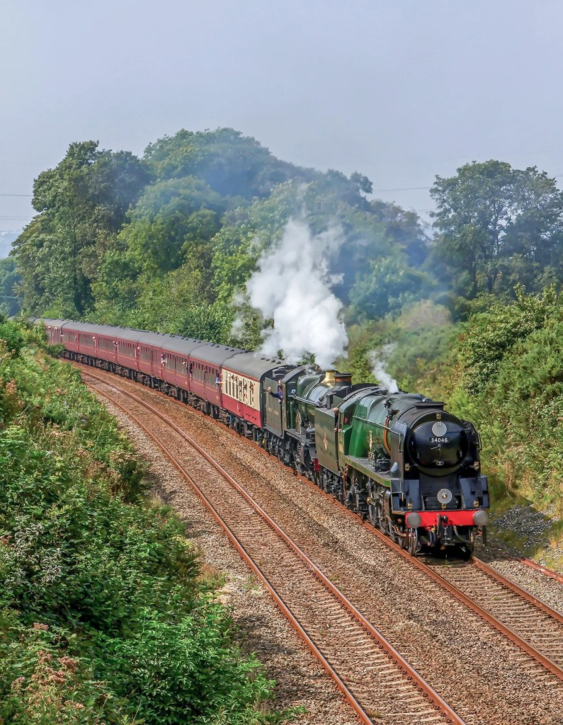Double headed steam locomotives BR Rebuilt Light Pacific 4-6-2 No: 34046 'Braunton' and GWR Castle Class 4-6-0 No: 5029 'Nunney Castle' are seen climbing Hemerdon Bank