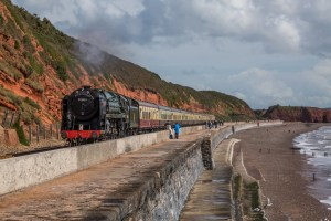 Steam locomotive train BR Standard Class 7MT4-6-2 No: 70000 'Britannia' is seen passing Dawlish. Steam train photography top tips.