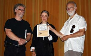 "RYT past president Mike Butler, receives a ""silver seat plaque"" from President Doug Barr and Sid Williams Theatre Manager, Deborah Renz."