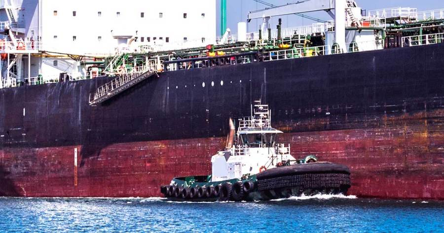 A tug boat is dwarfed beside an oil tanker.