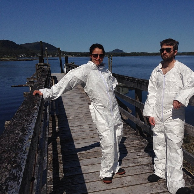 Two scientists in white lab suits standing casually leaning against a pier
