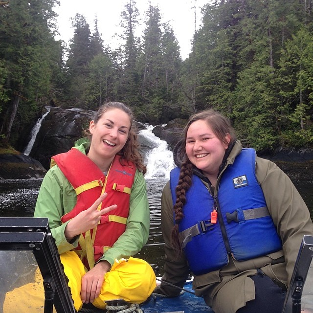 Raincoast scientists Lia and Ayla pose on a boat in front of a waterfall in search of bears in Heiltsuk territory