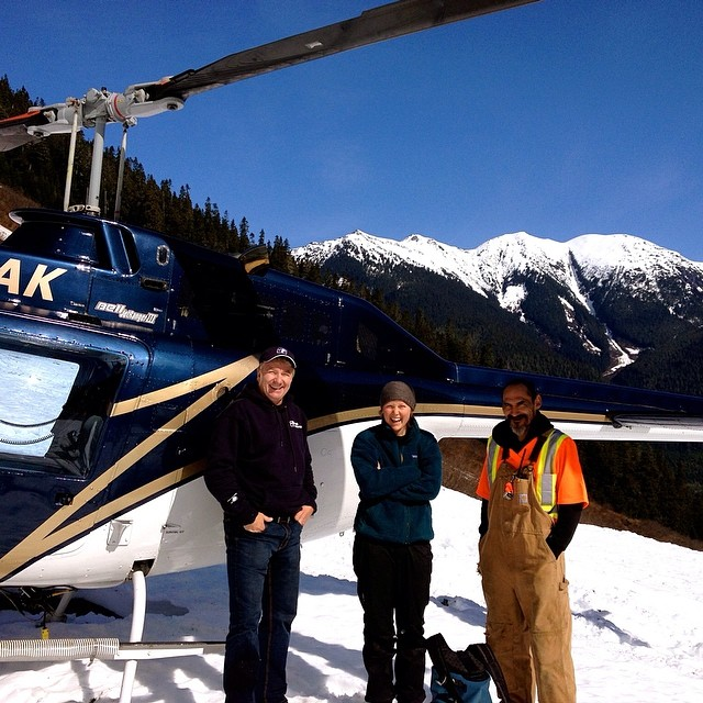 Two raincoast staff and the pilot stand beside the helicopter used for sampling in the Great Bear rainforest on Wuikinuxv Territory with snow on the ground and snow capped mountains in the background