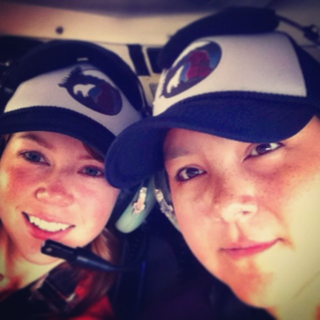 Two women wearing raincoast staff caps inside a helicopter