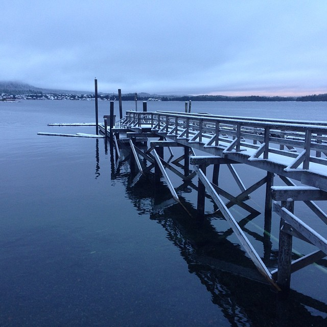 Light dusting of snow over pier jutting out into the water with a pale pink layer of sky over the horizon