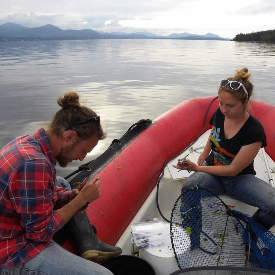 Two Raincoast scientists, one of them Justin Suraci on a zodiac boat