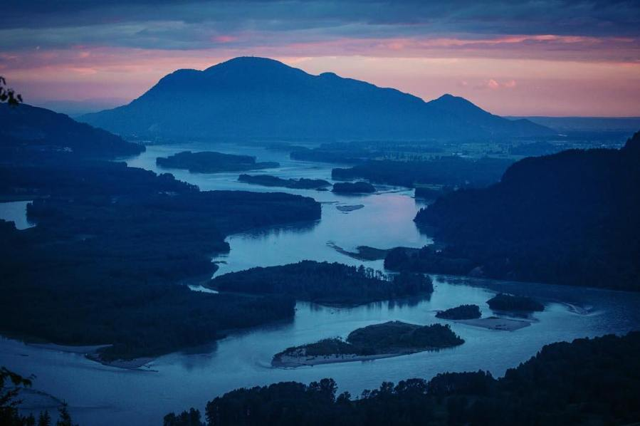 Winding white trail of Fraser River through the mountains in dark twilight
