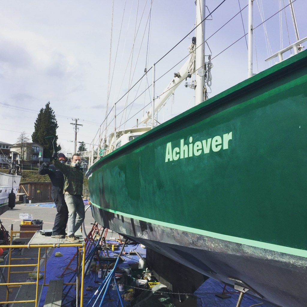 "A green boat lifted over a blue tarp with white writing on the side saying ""Achiever."" Two masculine people stand on a ladder beside the boat making happy, funny faces."