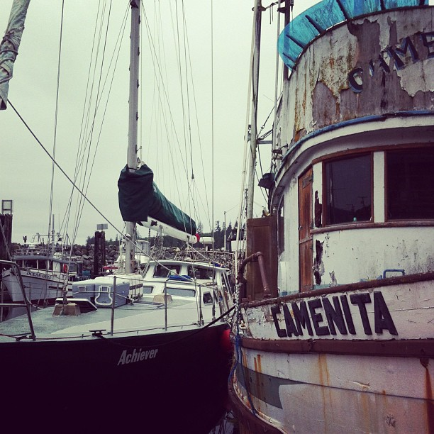 A sailboat with a green hull named Achiever in the marina next to a larger boat named Camenita. The latter is twice the size, and the panelling and paint are peeling off.