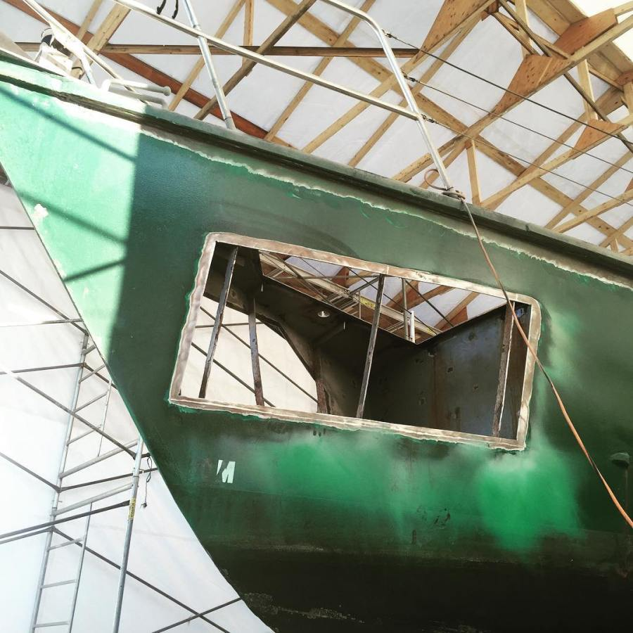 The hull of a green sailboat with a rectangular section cut out.