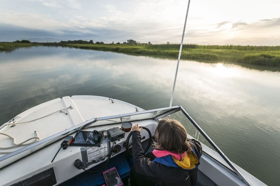 Looking down into the front of a sailboat and the person steering it. Past the boat is calm water and marshy green land to the right.