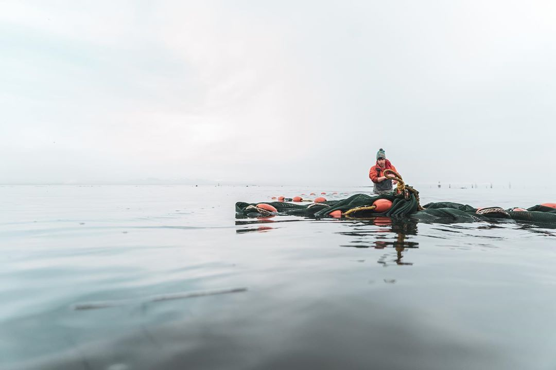A person in full rain gear crouches on a float of rope and buoy sitting on the water.