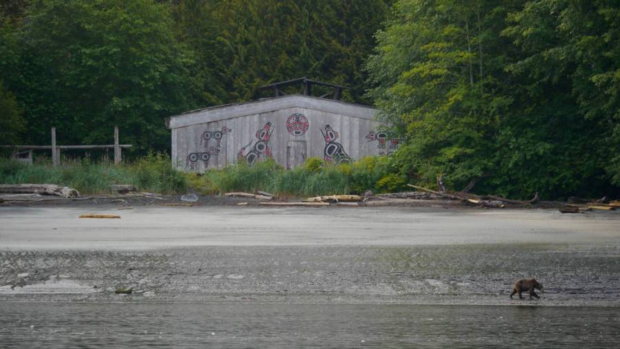 A wooden long house with a painted front built on a beach and surrounded by trees and fog.