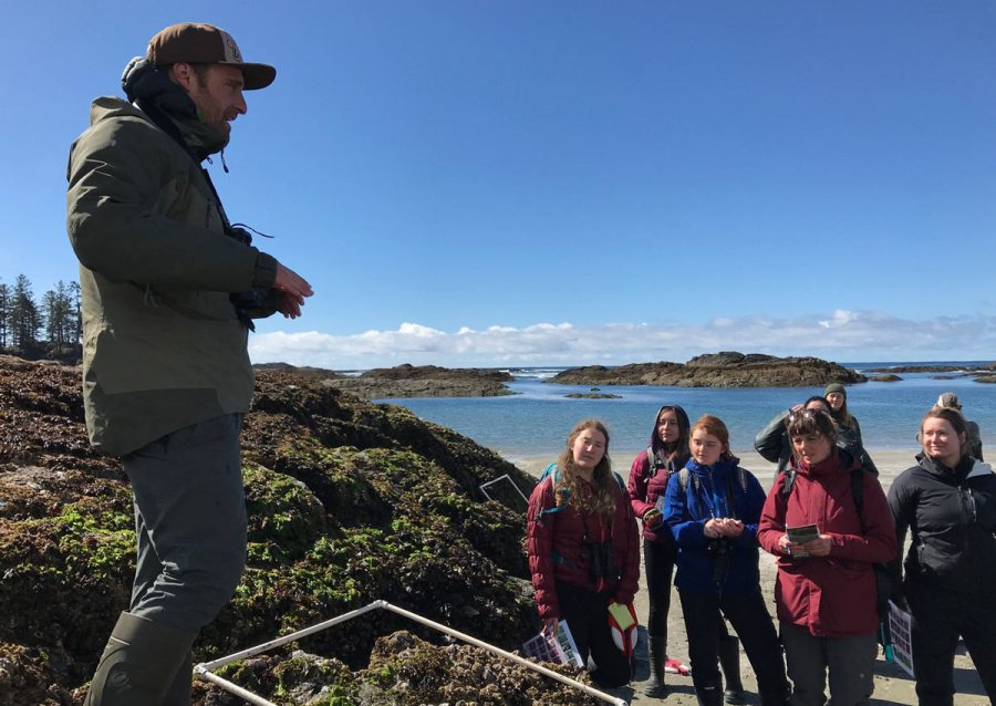 Nathaniel Glickman stands in front of a the Clayoquot Sound Field School participants on the beach on a sunny day.