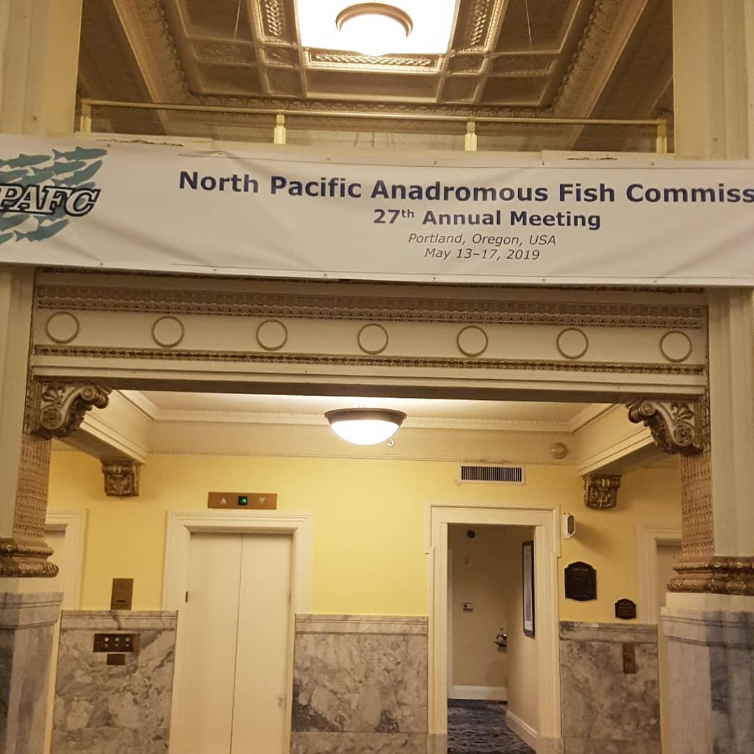 Hotel lobby with a banner hung across the wall which reads' North Pacific Anadromous Fish Commiss""