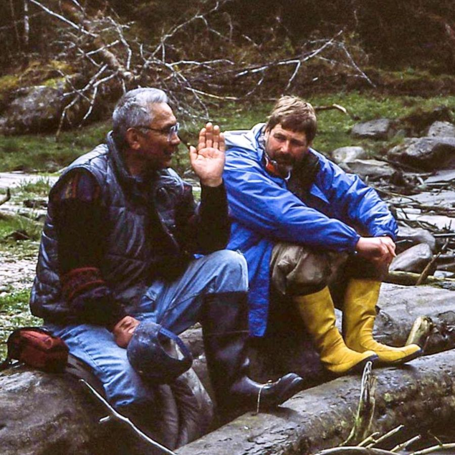 Two men sit on rocks by the water in deep discussion