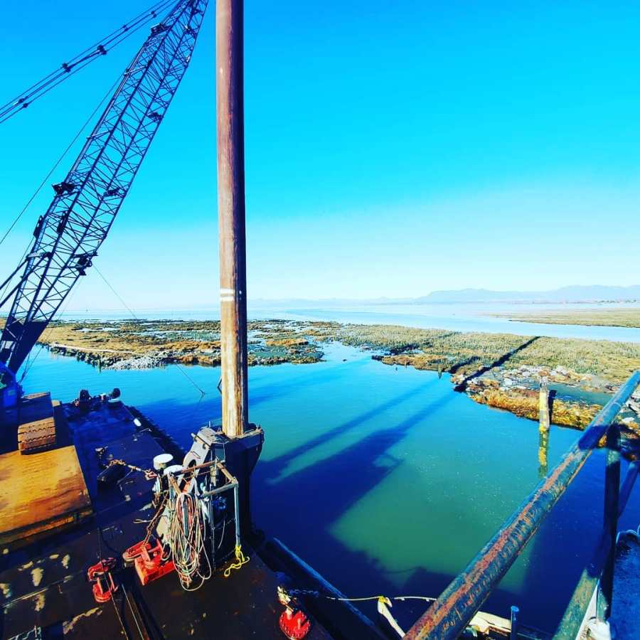 tall wooden pole connected to a crane looms over blue water with the shore visible on the other side under blue skies