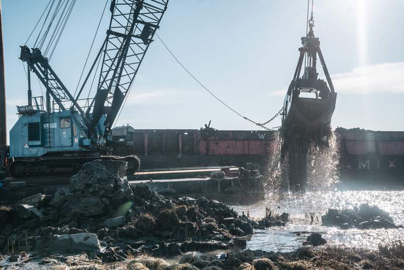 A blue cab lifts up the crane bucket of mud and water with water spilling down from it beside piles of rocks and grass at the jetty breach on Fraser River