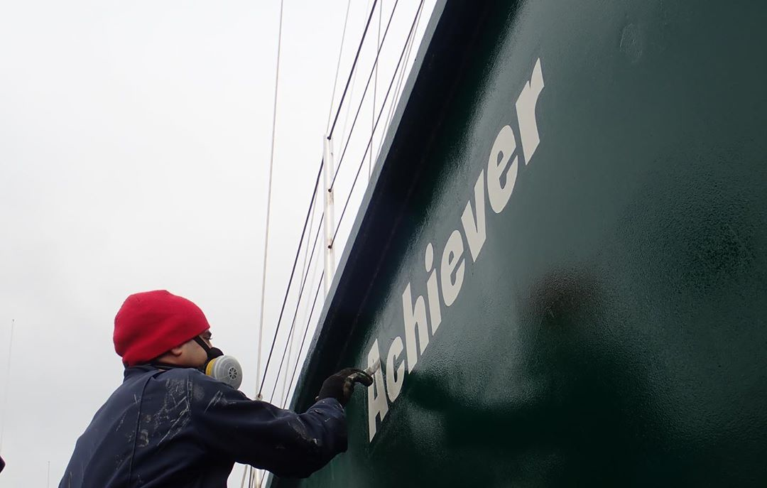 A painter in a red toque paints Achiever in white paint on the dark green side of the boat