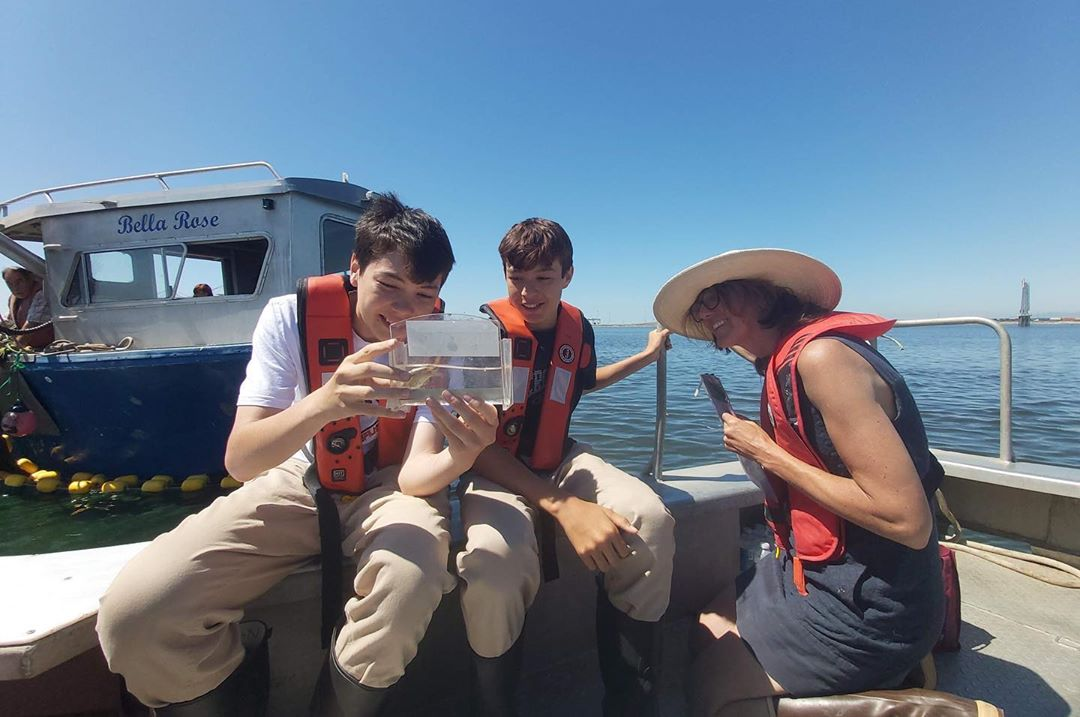 Two youth in matching red lifejackets and white t shirt and beige khakis sit on the deck of a boat examining juvenile salmon in a sampling box while scientist Misty wearing a wide brimmed white hat looks on