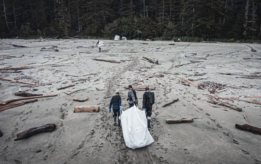 Three people seen from the air pulling garbage in a white bag along sand.