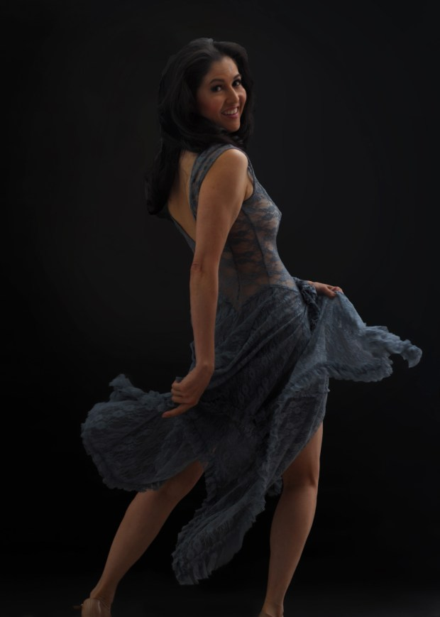 Exuberant woman dancing in dark lace dress with skirts flying.
