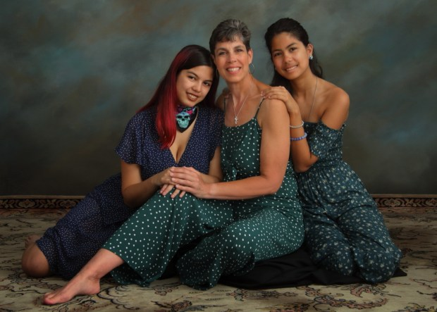 Smiling portrait of glamorous mom and her two daughters seated on a rug.
