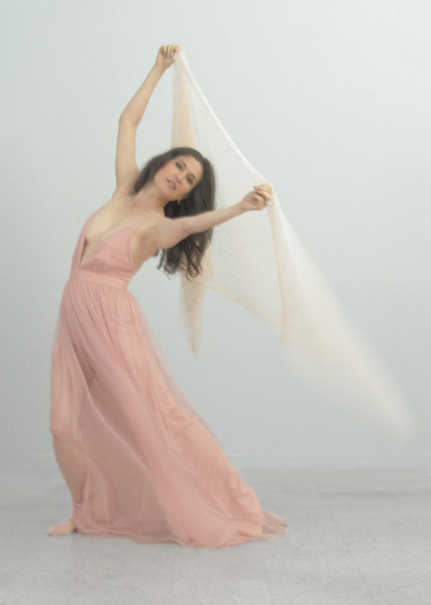 Woman in blush pink gown dancing sensuously with a scarf.