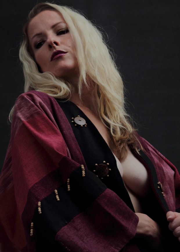 Bold and daring young woman posed seductively in vintage bolero jacket