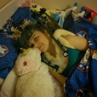 my little girl lying in bed with her cervical halo