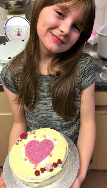 Boo proudly showing off the cake she made by herself