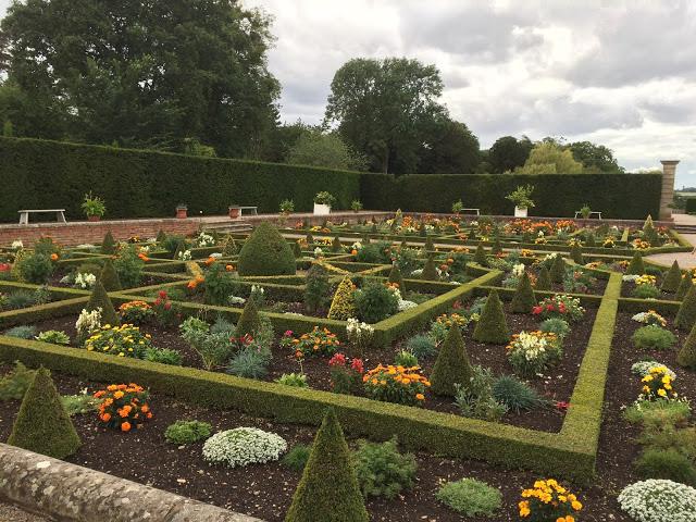 a sunken garden full of greenery and flowers
