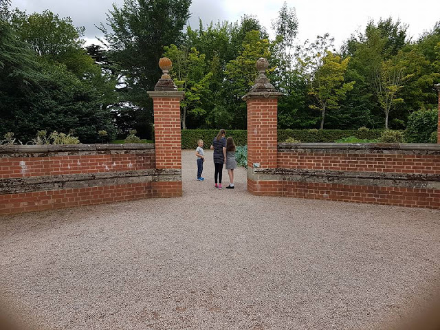 3 children entering the garden through a walled entrance