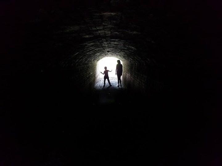 silhouette of two children in a dark tunnel