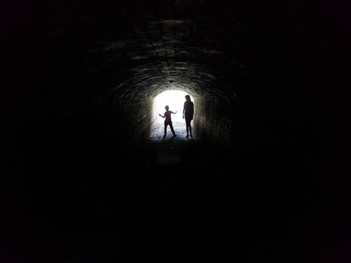 silhouette of two children in a dark tunnel