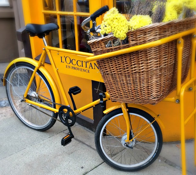 An old fashioned yellow bike with a basket of yellow flowers outside a shop painted yellow