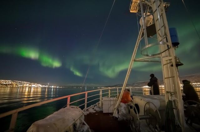 The front end of a boat sailing along a fjord with the Northern Lights glowing in the foreground.
