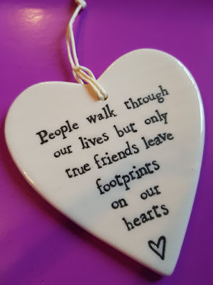 a ceramic heart with the text, people walk through our lives but only true friends leave footprints on our hearts
