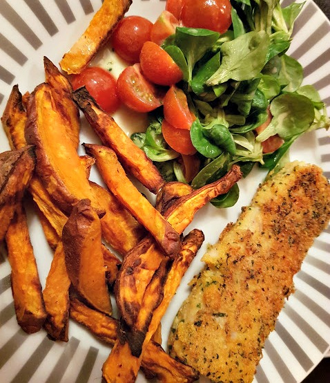 a plate of food, sweet potato chips, haddock and a small salad of tomato and lambs lettuce