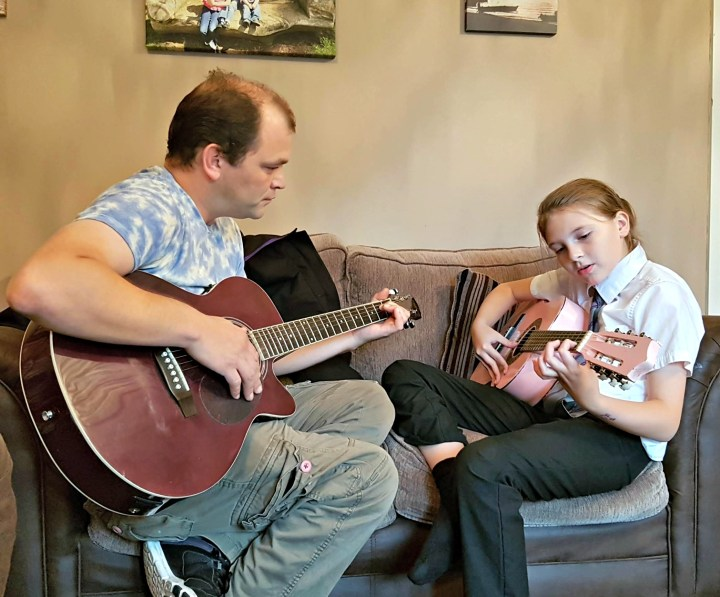 A dad and his daughter sitting on the settee, both with a guitar in their hands.