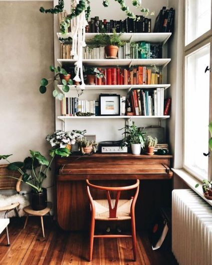 a dark wooden bench beneath a large bookshelf full of books and plants