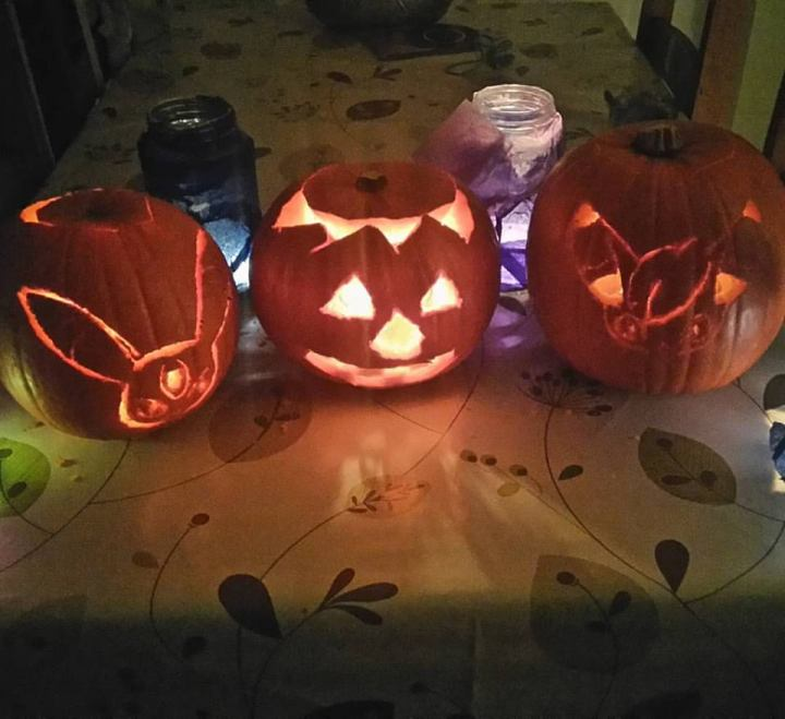 Three carved pumpkins lit up in the dark.